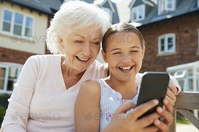 Granddaughter Showing Grandmother Mobile Phone On Visit To Retirement Home