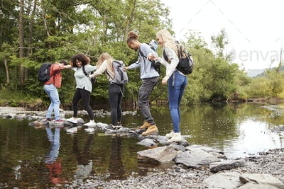 Multi ethnic group of five young adult friends hold hands balancing on rocks