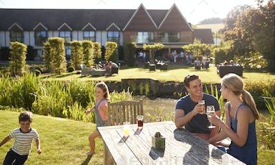 Family Enjoying Outdoor Summer Drink At Pub