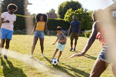 Adult family playing football with young son in garden