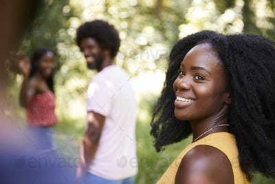 Young black woman in a forest with friends turning to camera
