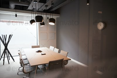 Chairs Around Boardroom Table In Empty Modern Meeting Room