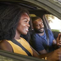 A young black man checks smartphone during a road trip