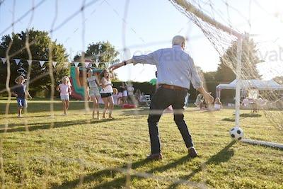 Children Playing Football Match With Senior Man At Summer Garden Fete