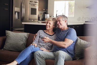 Senior white couple relaxing on couch watching television
