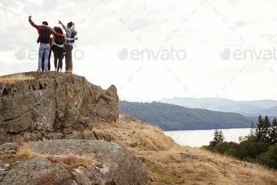 A group of five young adult friends embrace with arms in the air