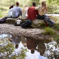Five young adult friends taking a break sitting on rocks by a stream during a hike