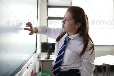 Female High School Student Wearing Uniform Using Interactive Whiteboard During Lesson