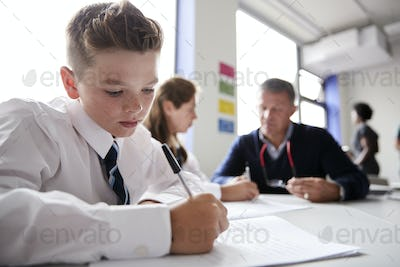 Male High School Student Wearing Uniform Working At Table