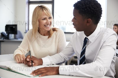 High School Tutor Giving Uniformed Male Student One To One Tuition At Desk In Classroom