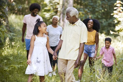 Senior black man and granddaughter walk with family in woods