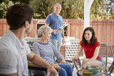 Senior couple and adult children barbecuing outside house