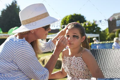 Girl At Face Painting Stall At Summer Garden Fete