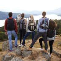 A group of five mixed race young adult friends admire the view after arriving at summit