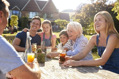Multi Generation Family Sitting At Table Enjoying Outdoor Summer Drink At Pub