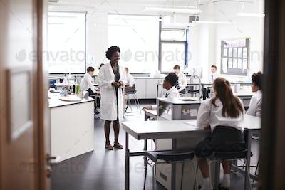 Female High School Tutor Teaching High School Students Wearing Uniforms In Science Class