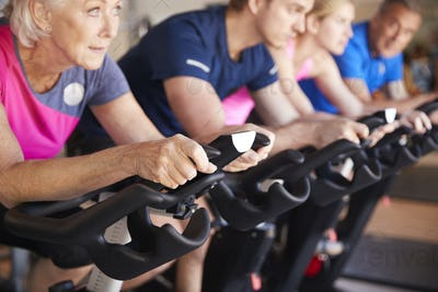 Close Up Of Group Taking Spin Class In Gym