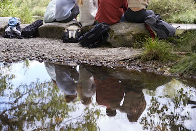 Reflection in stream of five young adult friends taking a break sitting on rocks during a hike