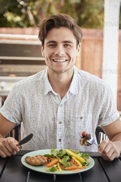 Young white man eating lunch at a table in the garden