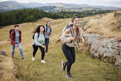 Multi ethnic group of five young adult friends hiking across a field uphill towards the summit