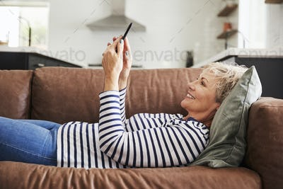 Senior white woman lying on couch at home using smartphone