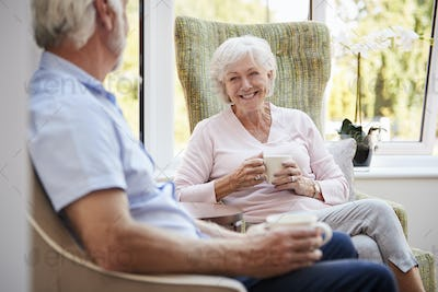 Senior Couple Sitting In Chairs And Chatting In Retirement Home