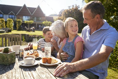 Grandparents With Grandchildren Enjoying Outdoor Summer Snack At Cafe