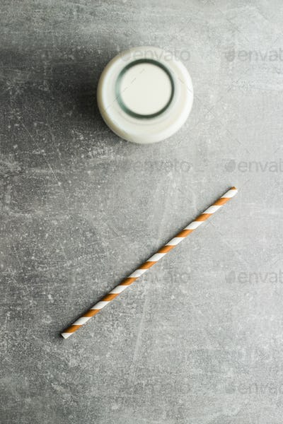 Striped straw and bottle of milk.