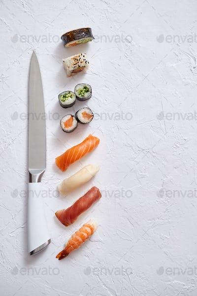 Various sushi rolls with Japanese knife on white stone slate background