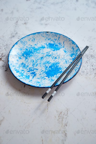 Blue hand painted ceramic serving plate with wooden chopsticks on side