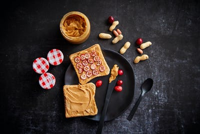 Toasts bread with homemade peanut butter served with fresh slices of cranberries