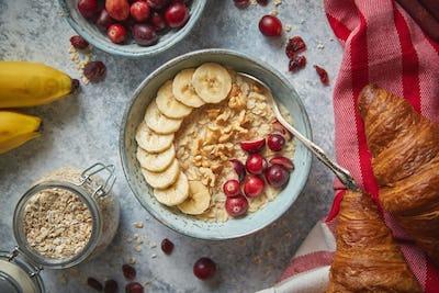 Ceramic bowl of oatmeal porridge with banana, fresh cranberries and walnuts