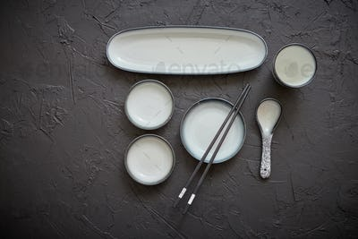 Set of empty ceramic dishes for sushi and rolls on a black stone table