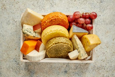 Fresh and delicious different kinds of cheeses placed in wooden crate with grapes