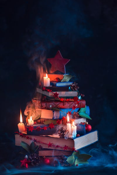 Christmas tree made out of books with candles and mysterious smoke. Winter decorations for readers