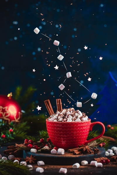 Marshmallow Ursa Major constellation with chocolate crumbs over a red cup of Christmas hot chocolate