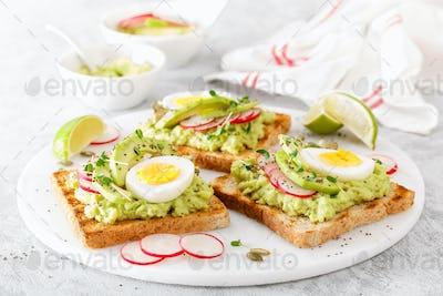 Sandwiches with avocado guacamole, fresh radish