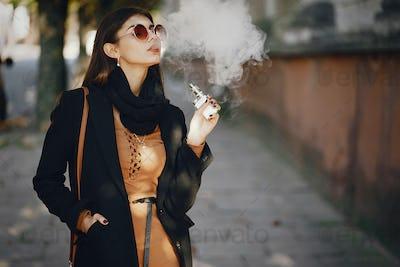 stylish girl smoking an e-cigarette