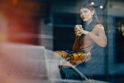 brunette girl drinking a hot beverage at a restaurant