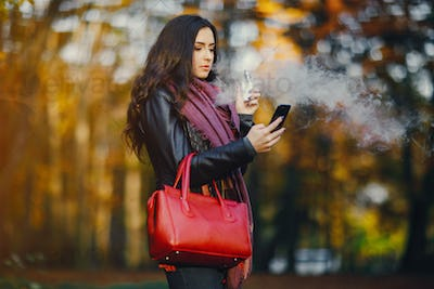 brunette girl is smoking an e-cigarette