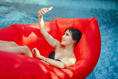 brunette girl using and talking on her phone in the pool
