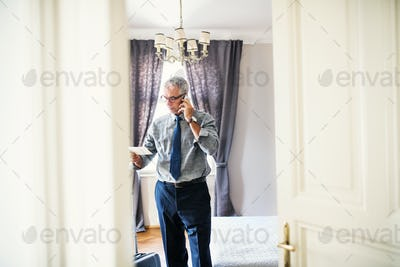 Mature businessman on a business trip standing in a hotel room, making phone call.