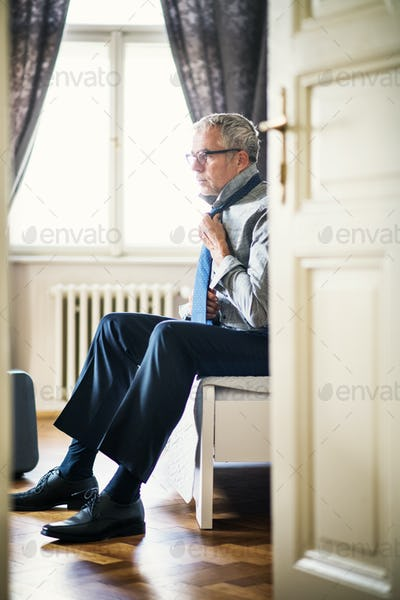 Mature businessman on a business trip in a hotel room, getting dressed.