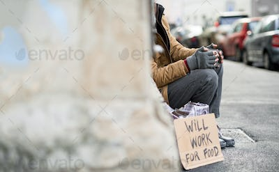 Homeless beggar man sitting outdoors in city asking for money donation. Copy space.