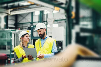 A portrait of an industrial man and woman engineer with tablet in a factory.