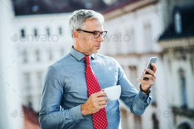 Mature businessman with smartphone standing on a terrace in city, texting.