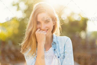 Gorgeous girl with a beautiful smile and sunrays reflected on he