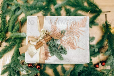 Gift box in wrapping paper, fir branch decoration