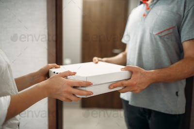 Pizza delivery man gives box to female client