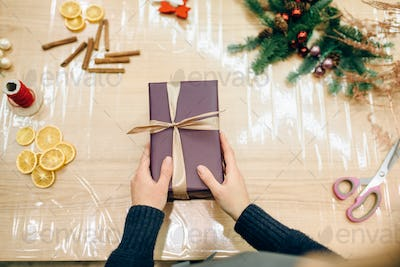 Female seller hands wrapping gift box, top view